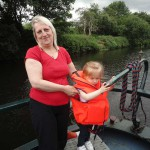 Woman with child steering boat